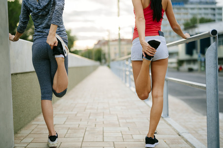 warm up exercise: Two women stretching feet before jogging Stock Photo