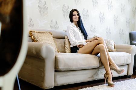 Elegante en vrouw, zittend op een bank in een luxe kamer en glimlachend Stockfoto
