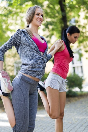 two woman: Beautiful women streching outdoors before setting off for their run