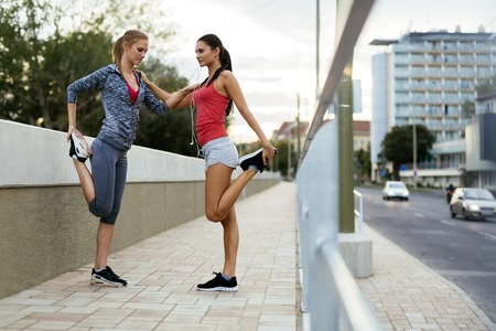 outdoor training: Two women stretching feet before jogging Stock Photo