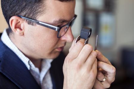 magnifying glass man: Jeweler examining diamond thoroughly through loupe Stock Photo