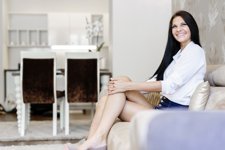 Elegant and sexy woman sitting on a sofa in a luxurious room and smiling