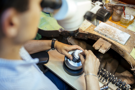 Jeweler working on metals with optical device that allows for precision work