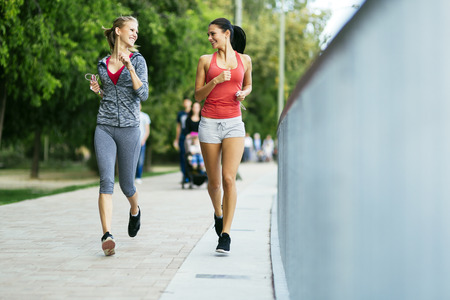 Two sporty women jogging in city while listening to music Stock Photo