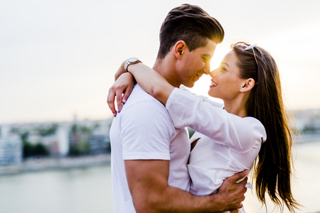 ロマンチックなカップルは若い美しい夕日でキスしようとしてハグ
