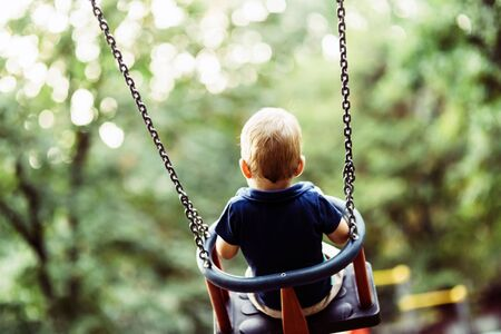 shot from behind: Playful child on swing outdoors, shot from behind Stock Photo
