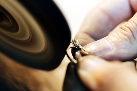 hands work: Jewelery polishing ring in workshop with adequate tools