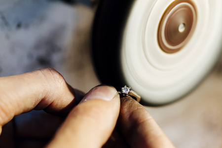 Jewelery polishing ring in workshop with adequate tools