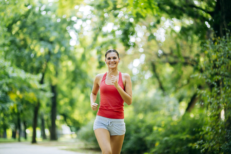 pursuing: Young beautiful athlete jogging in park and listening to some music while pursuing activity Stock Photo