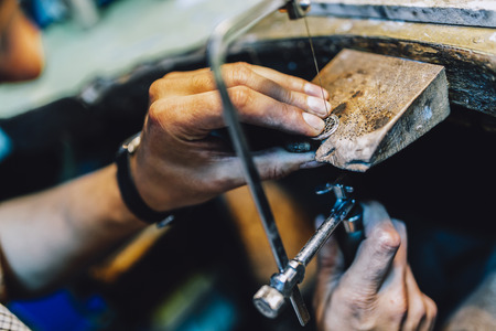 Jeweler making jewelry on workbench Foto de archivo