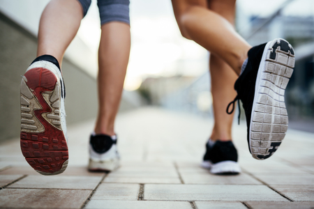 athlete running: Beautiful women jogging on pavement in city and feets are in focus