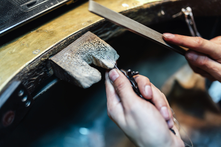 in jewelry: Jeweler working on a ring with precision tools