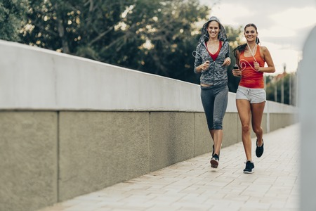 city of sunrise: Beautiful women jogging in city while sun is setting down Stock Photo