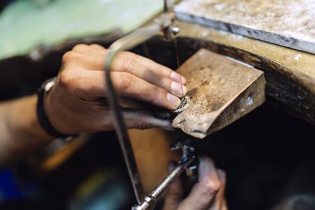 Jeweler making jewelry on workbench Imagens