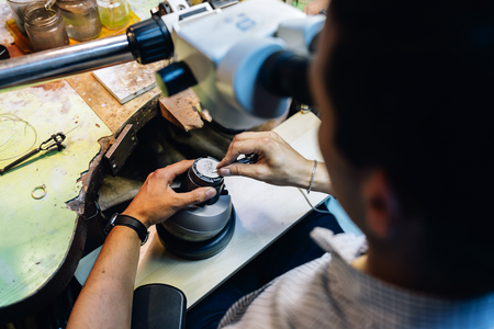 jeweler: Jeweler working on metals with optical device that allows for precision work