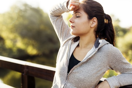 fatigued: Fatigued woman taking a break after jogging in nature Stock Photo