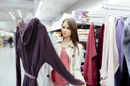 glancing: Beautiful woman glancing through clothes