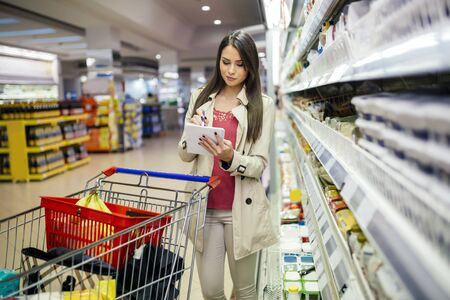 Beautiful woman shopping in supermarket and deciding what to buy
