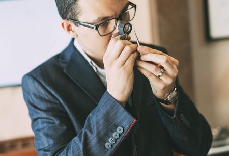 diamond: Jeweler examining diamond thoroughly through loupe Stock Photo