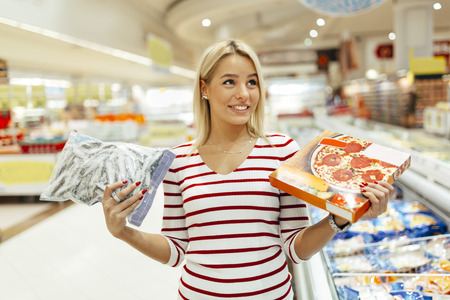 healthier: Beautiful woman deciding what to buy based on what is healthier