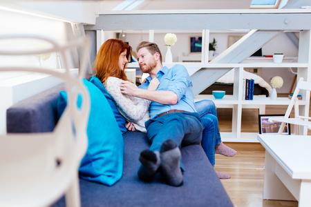 parejas romanticas: Pareja abrazos en el hermoso salón interior mientras está acostado en el sofá