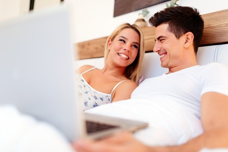 truly: Beautiful couple using laptop in bed while being truly happy