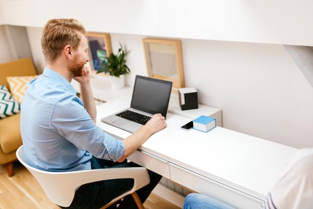 Handsome self-employed business working from home on a laptop Imagens