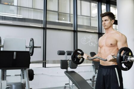 Muscular man bodybuilding in gym, lifting weights Stock Photo