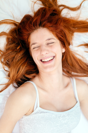 young adult woman: Portrait of a beautiful ginger woman smiling