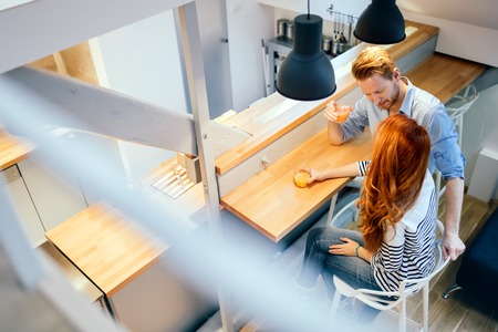 Beautiful couple talking in their pristine home while sitting at kitchen counter Stock Photo
