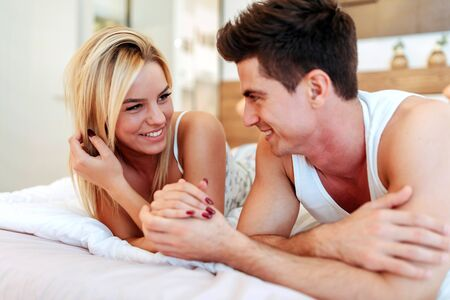 in: Happy husband loving wife while  lying in bed Stock Photo