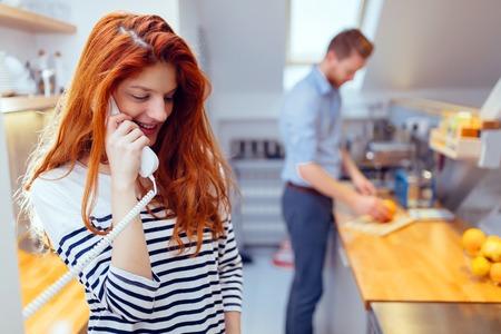 personas de pie: Gorgeus mujer jengibre hablando por tel�fono en la cocina