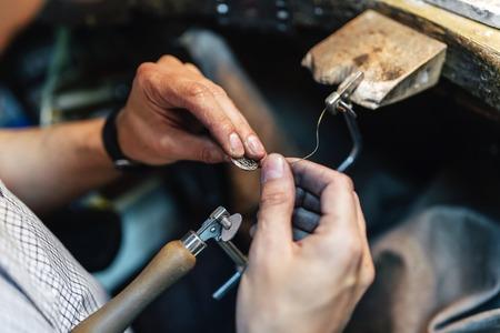 jewelry: Jeweler making jewelry on workbench Stock Photo