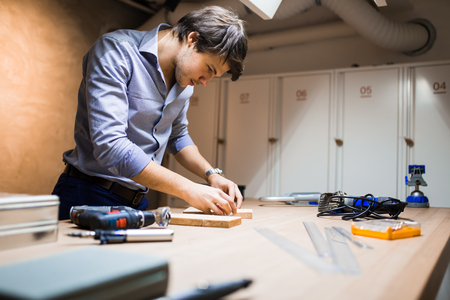 young adults: Joiner working and designing on workbench in workshop Stock Photo