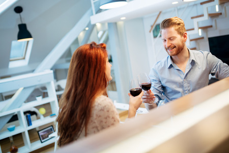 luxury apartment: Beautiful couple celebrating moving in to new apartment by toasting wine