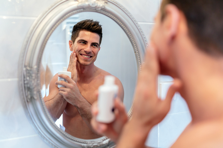 body male: Healthy positive male treating sking with lotion after shaving