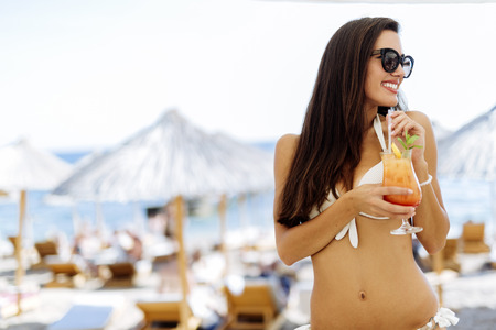 tan woman: Beautiful woman drinking cocktail on her vacation