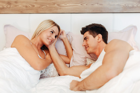 Couple in love lying on bed and touching each other tenderly Stock Photo