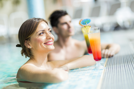 bikini couple: Young people drinking cocktails by the swimming pool and relaxing