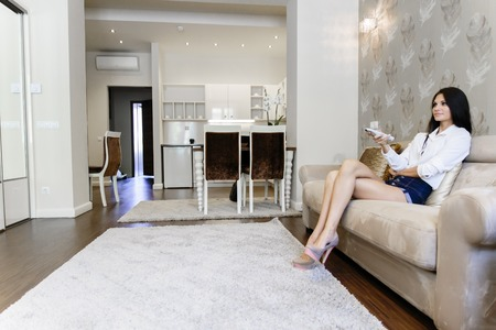 elegantly: Beautiful young woman using remote control in living room and dressed elegantly