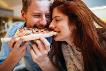 Couple sharing pizza and eating together happily