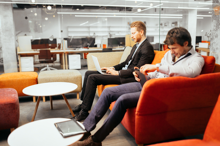 ejecutivo en oficina: Los empresarios que trabajan mientras mira a los dispositivos y ordenadores port�tiles