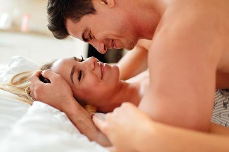 sexo pareja joven: Pareja juego previo sensual en la cama mientras est� acostado en la cama