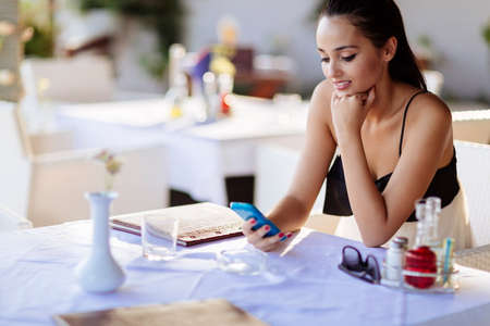 woman at the phone: Beautiful woman using phone in restaurant