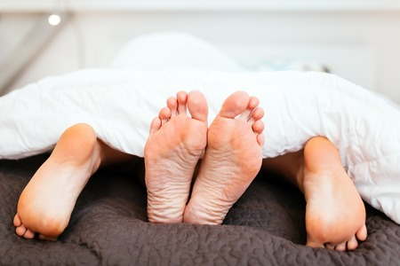 sex on bed: Couple having sex under blanket with their feet visible