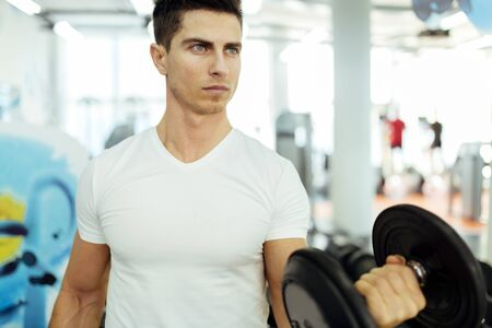 staying fit: Handsome man lifting weights in gym and staying fit