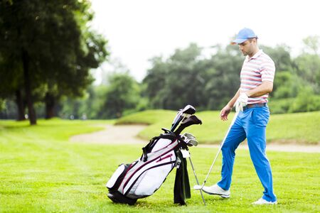 choosing selecting: Golfer selecting appropriate club for the next shot