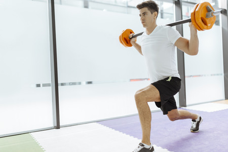 Handsome man exercising and lifting weights in fitness club Imagens