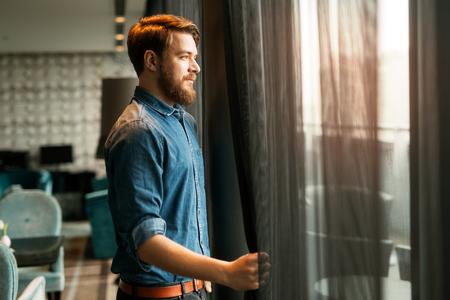 iluminado a contraluz: Apuesto hombre mirando el paisaje urbano a través de la ventana del rascacielos