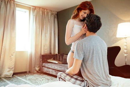sensual sex: Happy couple in bedroom enjoying sensual foreplay